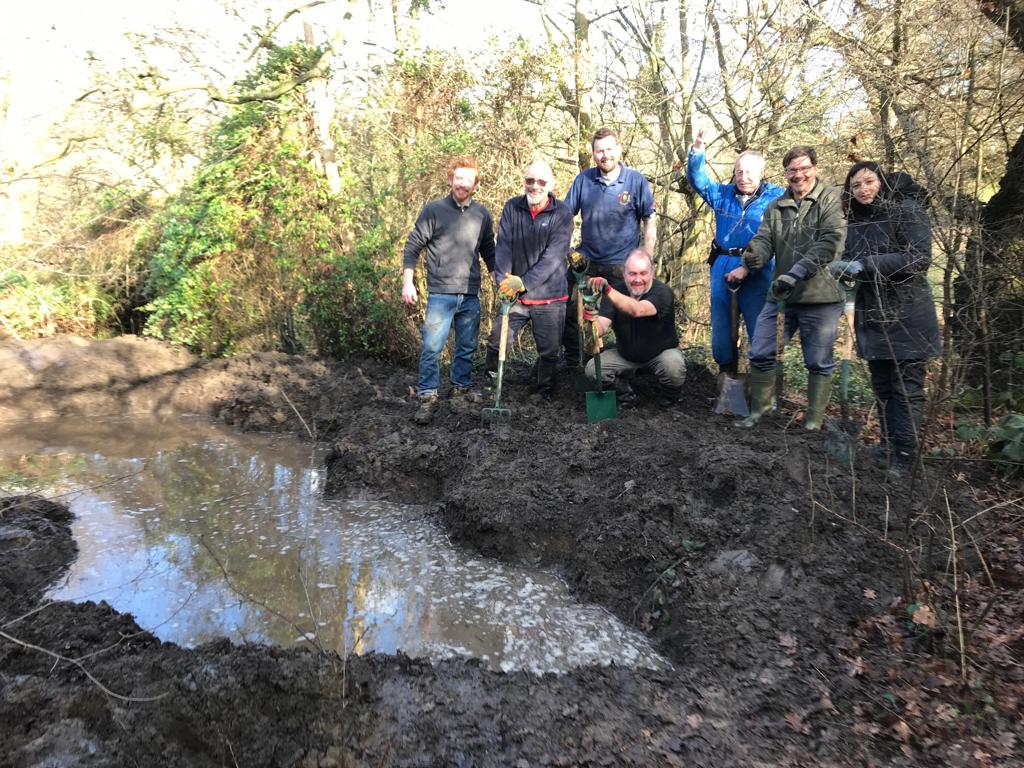 Volunteers proudly by the new pond