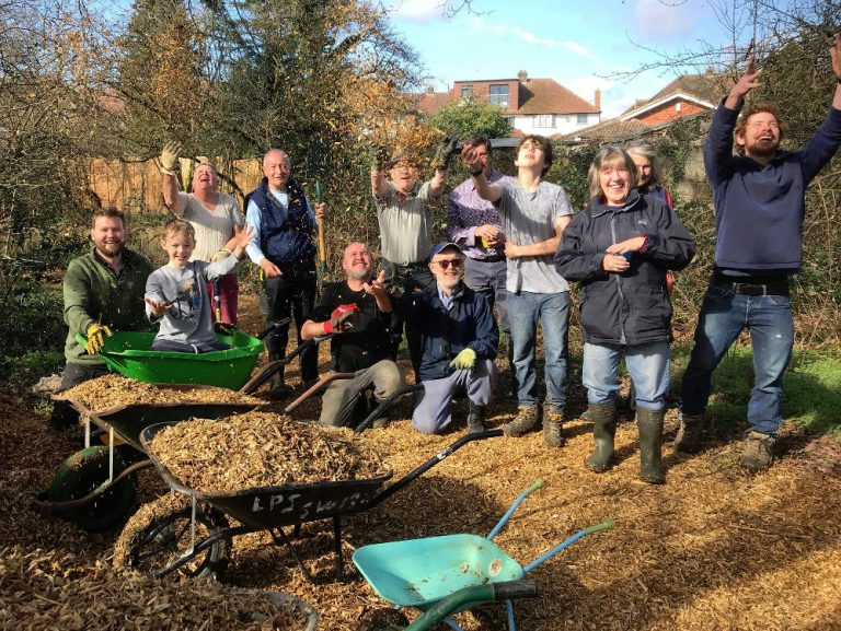 Volunteers posing for a group photo by pile of woodchip