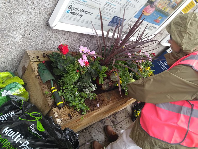 Planter near the station entrance being planted up