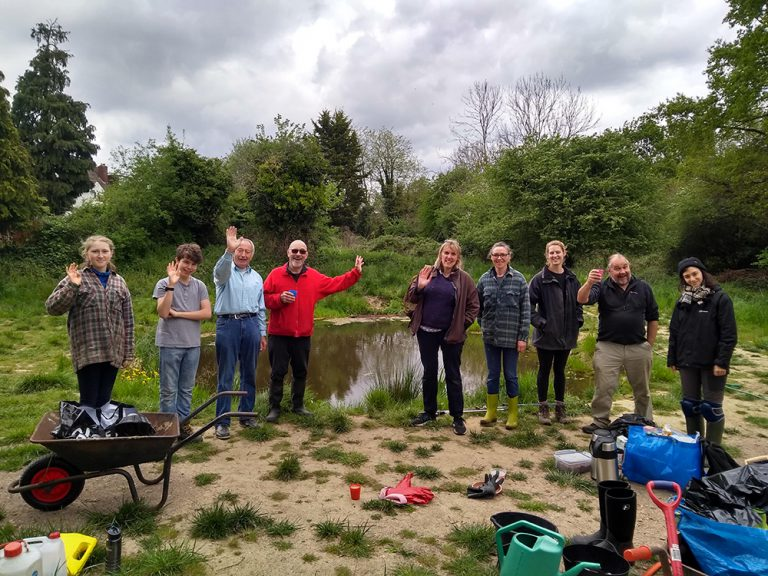 Volunteers posing for a group photo in fron of the algae free wildlife pond