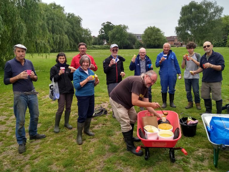 Volunteers posing for photo with their soup and baguettes