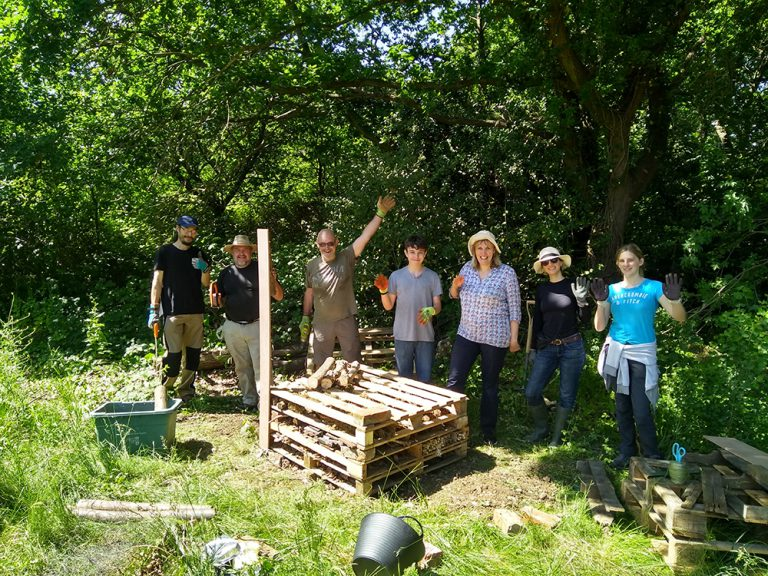 Volunteers posing for a group photo behind the beginnings of the bug hotel