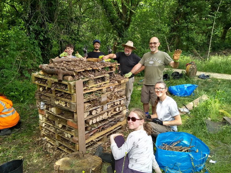 Volunteers posing fo a photo around the completed bug hotel
