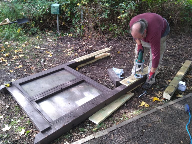 Volunteer reapiring noticeboard legs