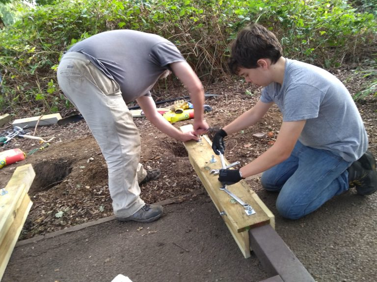 Volunteers bolting wooden post to existing legs