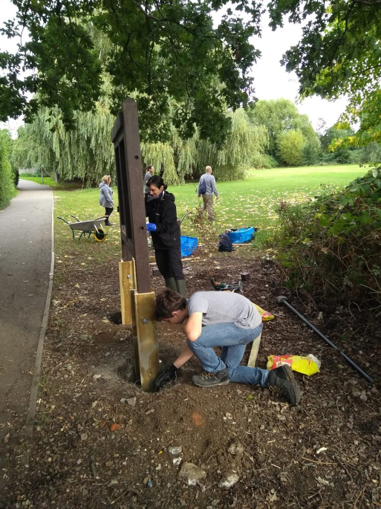 Volunteers working on the noticeboard with it back in position